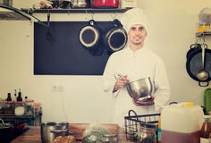Форма мужского кашевара нося работая на кухне Стоковые Фотографии RF