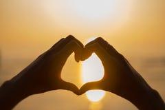 Форма сердца руки женщины в заходе солнца Стоковые Изображения RF
