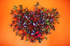 Форма сердца бабочек собирая на оранжевую предпосылку Стоковая Фотография RF
