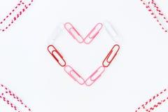 Форма сердца бумажными зажимами на белой предпосылке Стоковые Фотографии RF