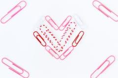 Форма сердца бумажными зажимами на белой предпосылке Стоковая Фотография