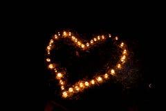 Форма сердца горящих свечей на том основании Стоковые Изображения