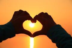 Форма сердца делая из рук против яркого захода солнца моря Стоковая Фотография RF