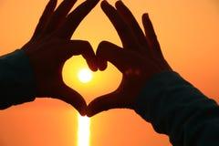 Форма сердца делая из рук против яркого захода солнца моря Стоковые Фото