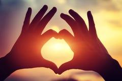 Форма сердца делая из рук против яркого захода солнца моря Стоковое Фото