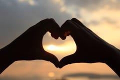 Форма сердца делая из рук против яркого захода солнца моря Стоковое Изображение