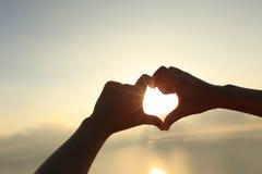 Форма сердца делая из рук против яркого захода солнца моря Стоковая Фотография