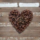 Форма сердца зажаренных в духовке кофейных зерен на деревянной предпосылке Стоковые Фотографии RF