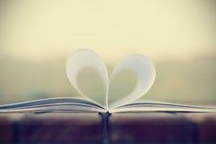 Форма сердца от бумажной книги на деревянном столе (винтажная предпосылка) Стоковая Фотография