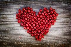 Форма сердца от красной смородины на естественной древесине Стоковые Фотографии RF