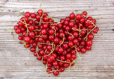 Форма сердца от красной смородины на естественной древесине Стоковое Изображение RF