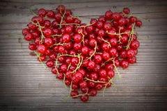 Форма сердца от красной смородины на естественной древесине Стоковые Изображения