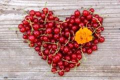 Форма сердца от красной смородины на естественной древесине Стоковое Фото