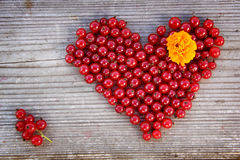 Форма сердца от красной смородины на естественной древесине Стоковая Фотография