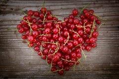 Форма сердца от красной смородины на естественной древесине Стоковое фото RF