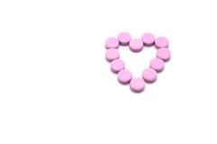 Форма сердца розовых пилюлек изолированных на белой предпосылке Стоковое Изображение RF