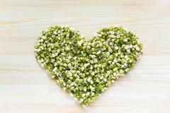 Форма сердца сделанная из зеленых фасолей mung с ростками на светлом woode Стоковые Фото