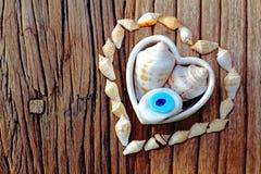 Форма сердца с раковиной моря и талисмана на backround деревянного стола Стоковые Фото