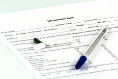 Форма страхования жизни Немного пилюлек и ручка на листе стоковые изображения