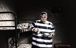 Форма тюрьмы сердитого пленника нося держа алюминиевые блюда внутри Стоковое Фото