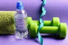Формировать и фитнес Штанги около бутылки с водой и мягкого полотенца стоковые фотографии rf
