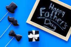 Формулирует счастливый день ` s отца написанный на классн классном Печенья черного галстука, усика и шляпы Голубое взгляд сверху  Стоковые Изображения RF