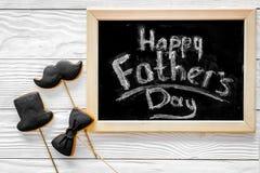 Формулирует счастливый день ` s отца написанный на классн классном Печенья черного галстука, усика и шляпы Белое деревянное взгля Стоковые Фото