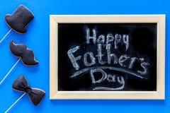 Формулирует счастливый день ` s отца написанный на классн классном Печенья черного галстука, усика и шляпы Голубое взгляд сверху  Стоковое Изображение