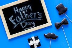 Формулирует счастливый день ` s отца написанный на классн классном Печенья черного галстука, усика и шляпы Голубое взгляд сверху  Стоковые Фотографии RF
