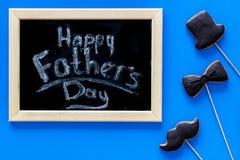 Формулирует счастливый день ` s отца написанный на классн классном Печенья черного галстука, усика и шляпы Голубое взгляд сверху  Стоковая Фотография RF