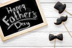 Формулирует счастливый день ` s отца написанный на классн классном Печенья черного галстука, усика и шляпы Белое деревянное взгля Стоковые Фотографии RF