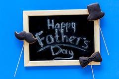 Формулирует счастливый день ` s отца написанный на классн классном Печенья черного галстука, усика и шляпы Голубое взгляд сверху  Стоковая Фотография
