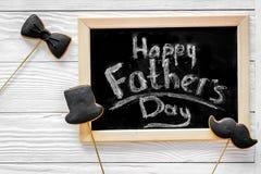 Формулирует счастливый день ` s отца написанный на классн классном Печенья черного галстука, усика и шляпы Белое деревянное взгля Стоковое фото RF