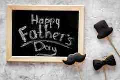 Формулирует счастливый день ` s отца написанный на классн классном Печенья черного галстука, усика и шляпы Серое каменное взгляд  Стоковое фото RF