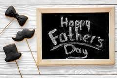 Формулирует счастливый день ` s отца написанный на классн классном Печенья черного галстука, усика и шляпы Белое деревянное взгля Стоковое Фото