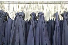 Формы рубашек работы синего воротничка на вешалках Стоковые Фотографии RF
