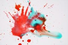 Фосфоресцентный зеленый красный выплеск акварели на белой предпосылке Стоковое фото RF