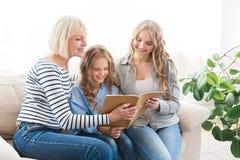 Фотоальбом счастливой бабушки наблюдая с ее дочерью и внуком стоковые фото