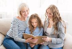 Фотоальбом счастливой семьи наблюдая на софе стоковое фото rf