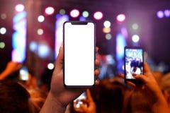 Фотографировать концерт музыки с умным телефоном от аудитории стоковые фото