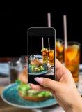 Фотографирующ концепцию еды - женщина фотографирует сандвич с бургером, сыром и салатом цыпленка Стоковая Фотография