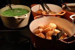Фотография еды больших лотков или баков заполнила с горячими сваренными горохами и подливкой кудрявых картошек жаркого зелеными н Стоковое Фото