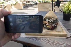 Фотография еды вкусного черного бургера в кафе outdoors человек Хан стоковое изображение