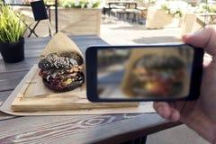 Фотография еды вкусного черного бургера в кафе outdoors человек Хан стоковая фотография