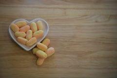 Фотография еды для валентинок с белым блюдом формы сердца влюбленности заполнила с помадками сахара конфеты в желтых и оранжевых  Стоковая Фотография RF