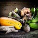 Фотография искусства натюрморта на плодоовощах с человеческой смертью черепа стоковая фотография