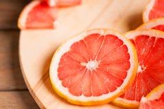 Фотография куска грейпфрута на деревянной разделочной доске Стоковое Изображение