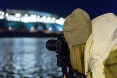 Фотография ночи девушки DSLR и тренога на городском речном береге Стоковое Изображение RF