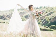 Фотография свадьбы изящного искусства Красивая невеста с букетом и платье с поездом в природе Стоковое Фото