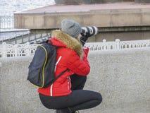 Фотограф девушки в красной куртке Стоковое Изображение RF